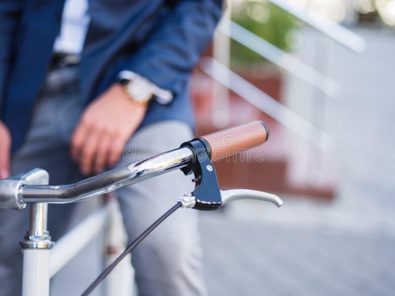 Młody elegancki biznesmen iść pracować rowerem outdoors obraz royalty free