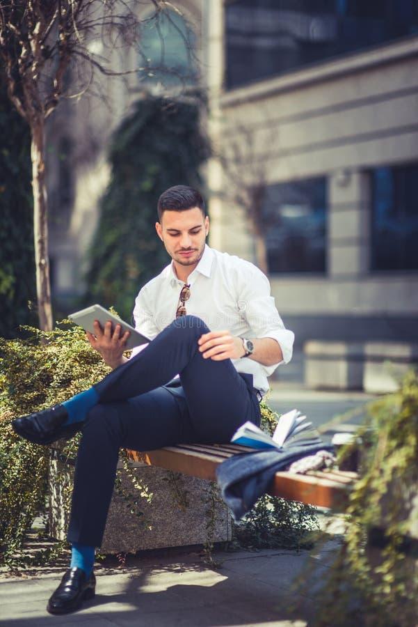 Młody elegancki biznesmen używa komputer osobisty pastylkę podczas gdy siedzący na ławce zdjęcia royalty free