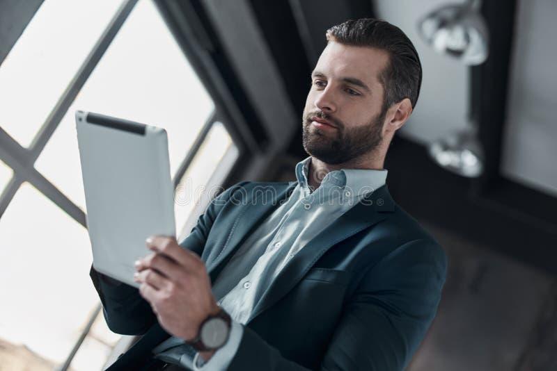 Młody elegancki biznesmena lider indoors przy biura używać cyfrowy obraz royalty free