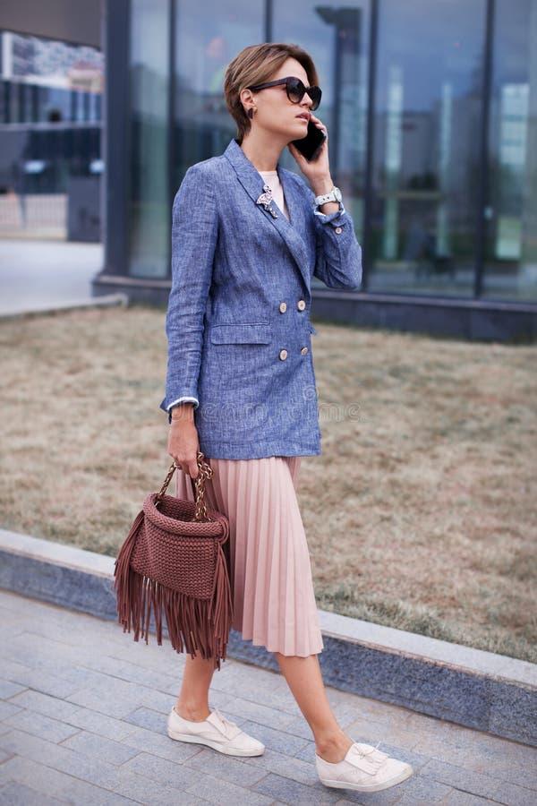 Młody elegancki bizneswoman opowiada telefonem komórkowym outside Pełny długość portret Kaukaski kobieta model fotografia royalty free