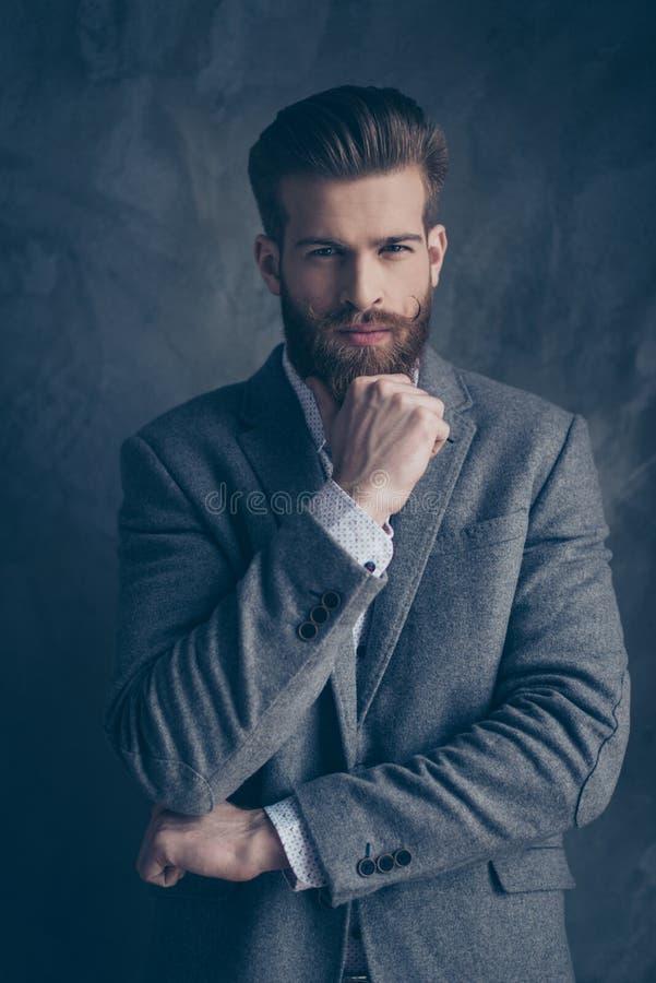 Młody elegancki brodaty facet z wąsy w kostiumu stojakach na gr fotografia stock