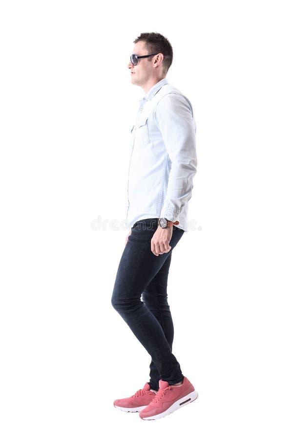Młody elegancki dorosły mężczyzna chodzi naprzód i patrzeje z okularami przeciwsłonecznymi Boczny widok obrazy stock