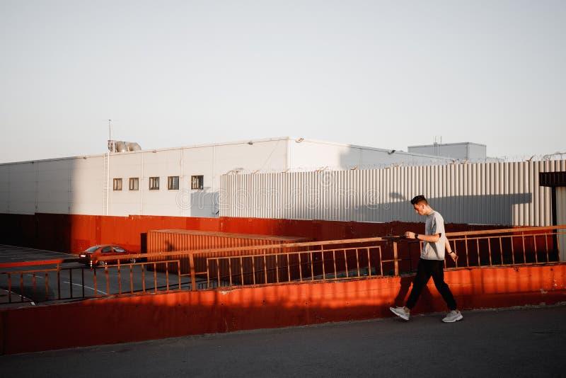 Młody elegancki facet ubierający w cajgach i białej koszulce chodzi obok miastowego budynku z parking w zmierzchu obrazy stock