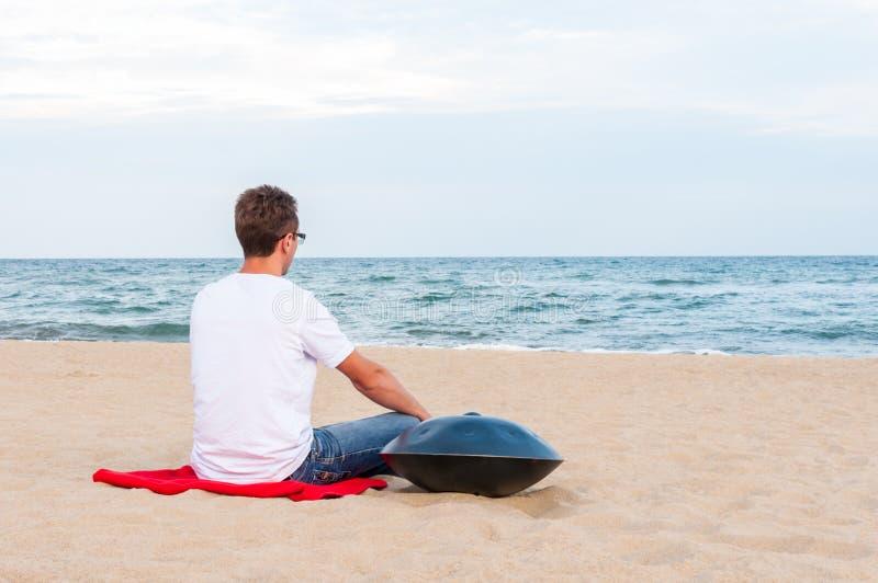 Młody elegancki faceta obsiadanie na piasek plaży blisko handpan lub zrozumienie z morzem Na tle Zrozumienie jest tradycyjny etni zdjęcie royalty free