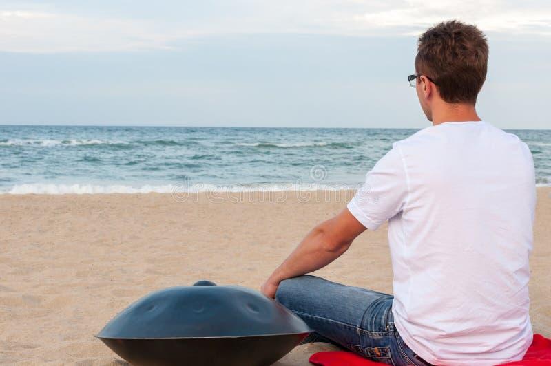 Młody elegancki faceta obsiadanie na piasek plaży blisko handpan lub zrozumienie z morzem Na tle Zrozumienie jest tradycyjny etni fotografia stock