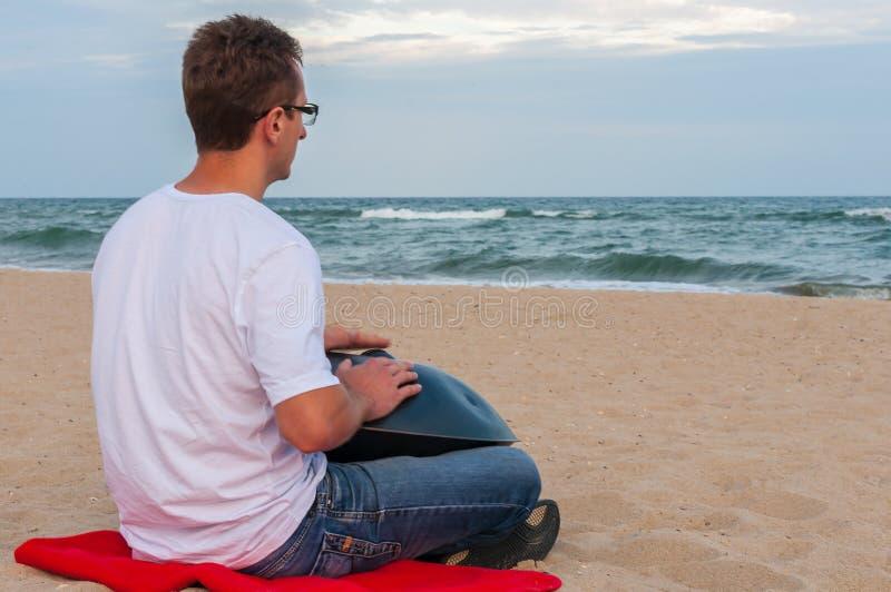 Młody elegancki faceta obsiadanie na, zrozumienie z morzem Na tle piaska bawić się i lub Zrozumienie jest tradycyjny obrazy royalty free