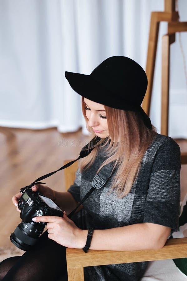 Młody elegancki kobieta fotograf sprawdza fotografie na kamerze w studiu obraz royalty free