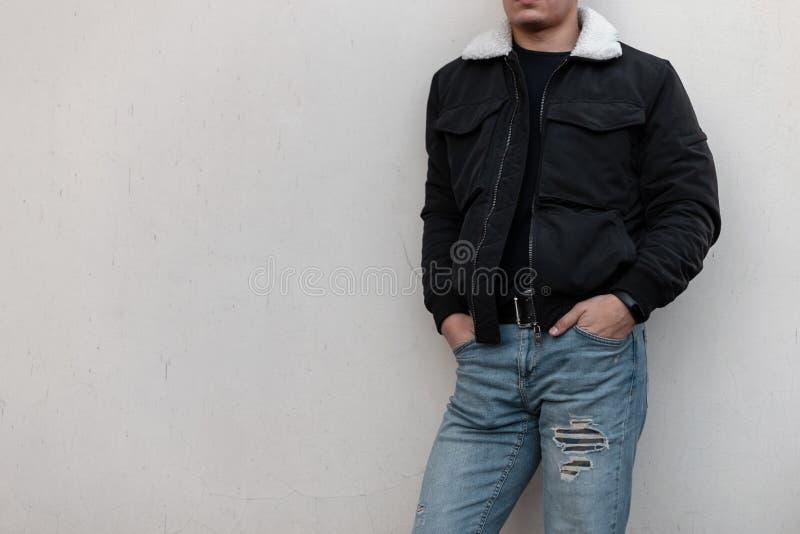 M?ody elegancki m??czyzna w czarnej modnej kurtce z urz?dniczym w rocznik?w niebieskich d?insach w koszulki czarnych stojakach bl fotografia royalty free