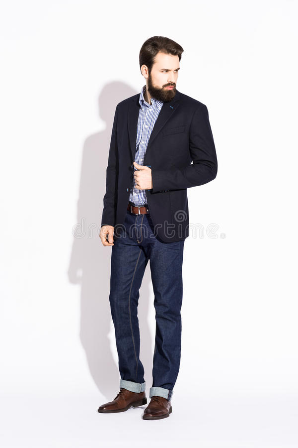 młody elegancki mężczyzna z brodą, ubierającą w studiu na bielu zdjęcia stock
