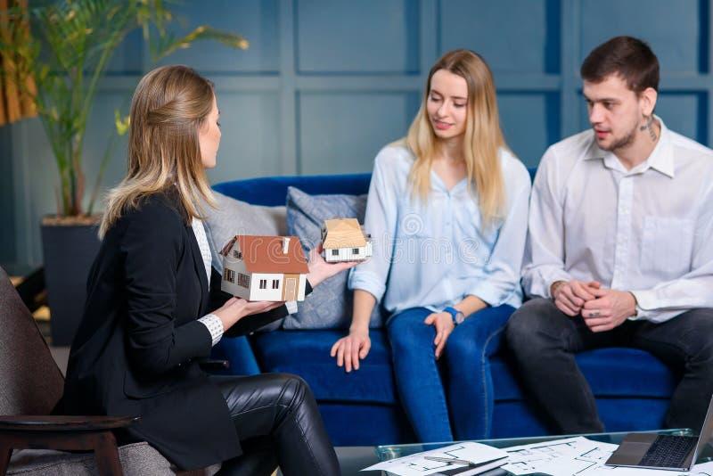 Młody elegancki pośrednik handlu nieruchomościami, projektant wnętrz, decorator opowiada z parą klienci fotografia royalty free
