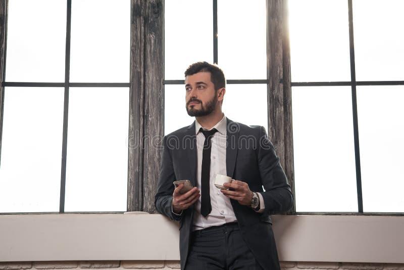 Młody elegancki przystojny biznesmen stoi bezczynnie okno przy jego biurem ma kawową przerwę i trzyma telefon komórkowego w jego obraz royalty free