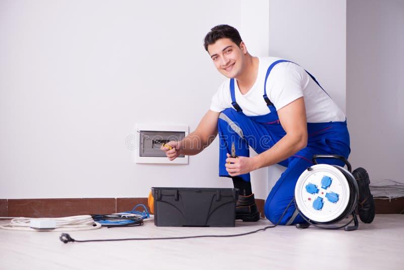 Młody elektryk pracuje na nasadce w domu zdjęcie stock