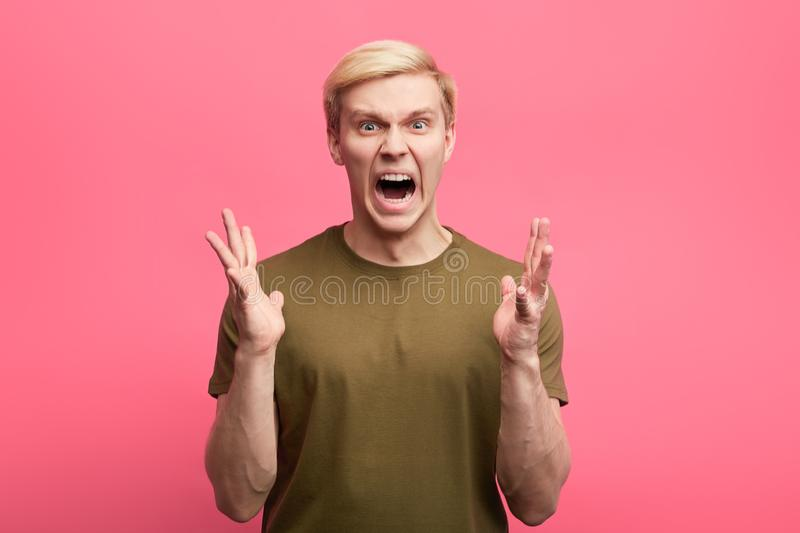 Młody emocjonalny mężczyzna z agresywnym wyrażeniem i ręki podnosić zdjęcia royalty free