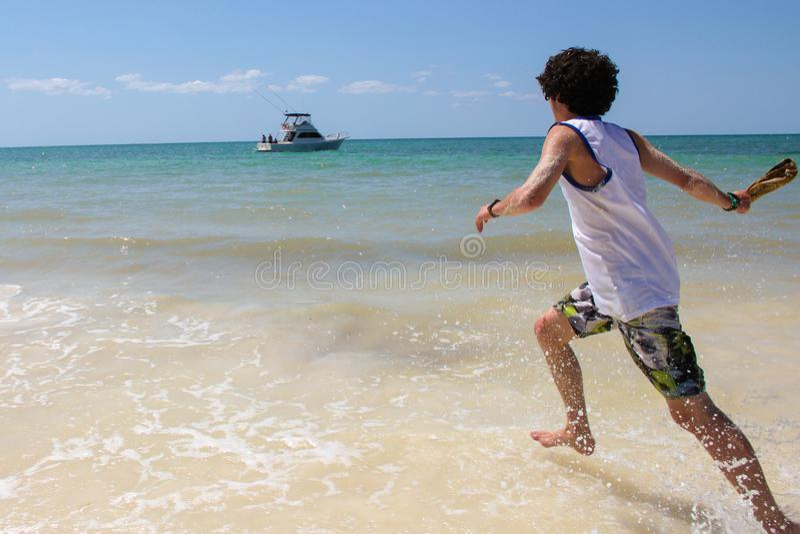 Młody facet biega w morze zdjęcia royalty free