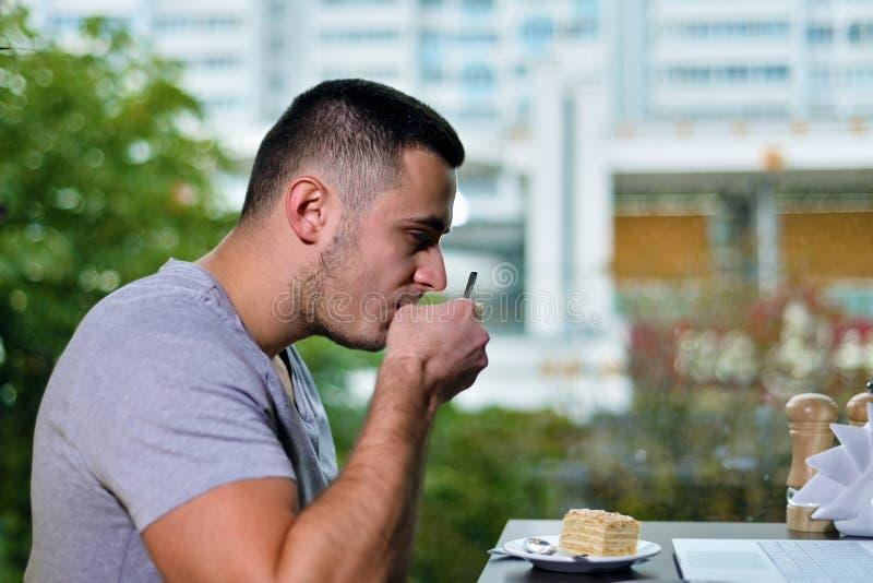 Młody facet jest freelancer w cukiernianym działaniu za laptopem pijesz kawy zdjęcie royalty free