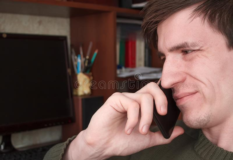 Młody facet opowiada na czarnym smartphone z uśmiechem, dobre wieści fotografia stock