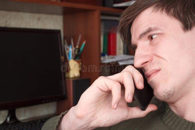 Młody facet opowiada na czarnym smartphone z uśmiechem, dobre wieści obraz royalty free