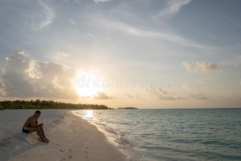 Młody facet siedzi na piaskowatej plaży i myśleć o coś fotografia stock