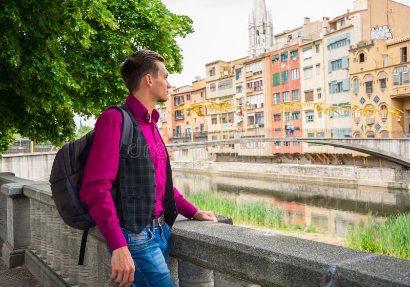 Młody facet, turysta, stojaki z plecakiem na brzeg rzeki O fotografia royalty free