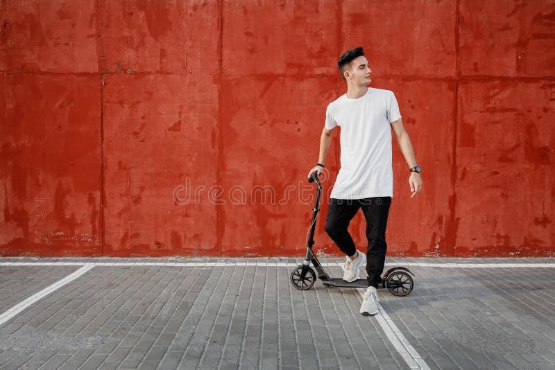 Młody facet ubierał w cajgach i koszulka stojakach z hulajnogą przeciw malującej betonowej ścianie na letnim dniu w fotografia stock