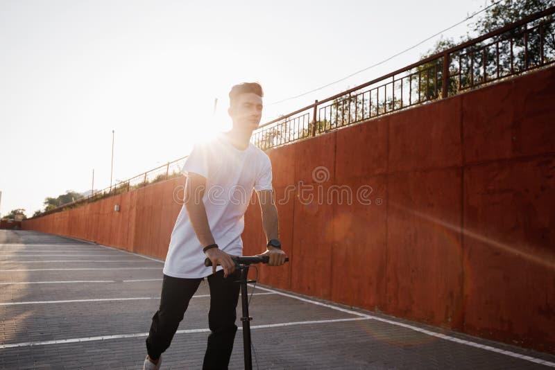 Młody facet ubierający w cajgach i koszulce jedzie hulajnogę przeciw malującej betonowej ścianie na słonecznym dniu w mieście obrazy royalty free
