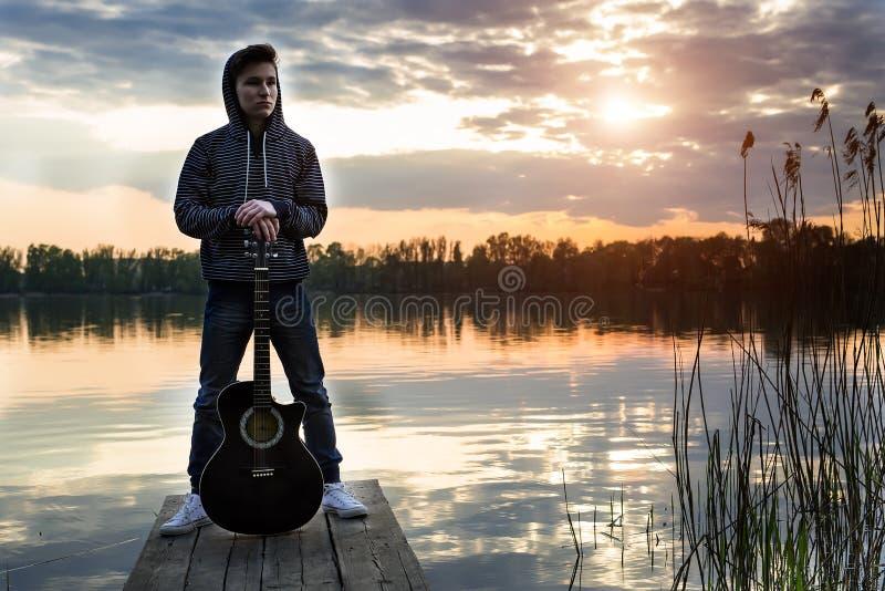 Młody facet w kapiszon pozyci z jego gitarą na moscie w wieczór przeciw tłu zmierzch na rzece obraz stock