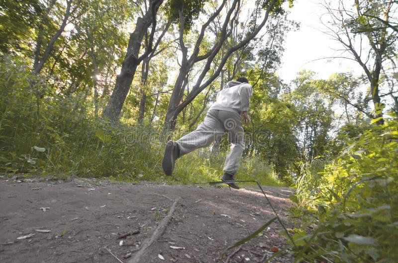 Młody facet w szarości bawi się kostiumów bieg wzdłuż ścieżki wśród obraz royalty free