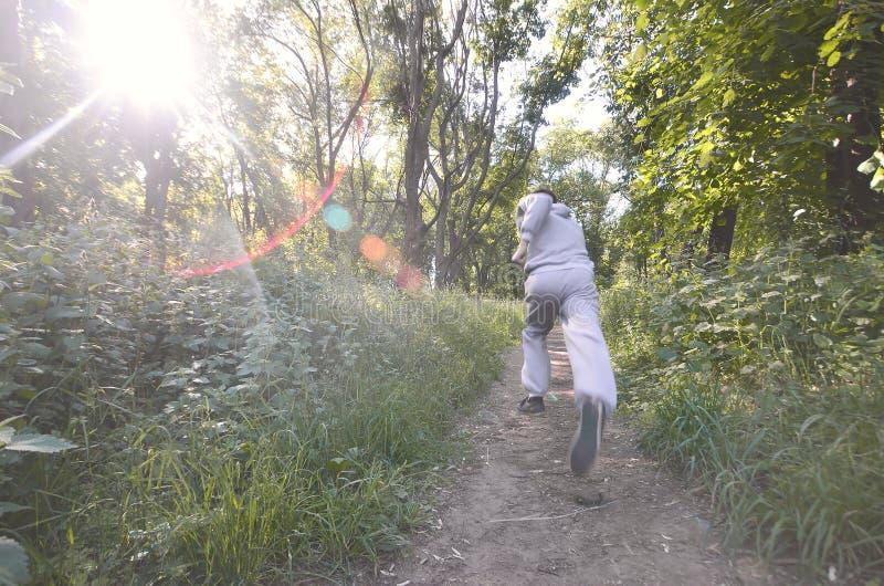 Młody facet w szarości bawi się kostiumów bieg wzdłuż ścieżki wśród zdjęcia royalty free