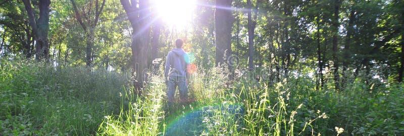 Młody facet w szarości bawi się kostiumów stojaki naprzeciw słońca wśród zdjęcia royalty free
