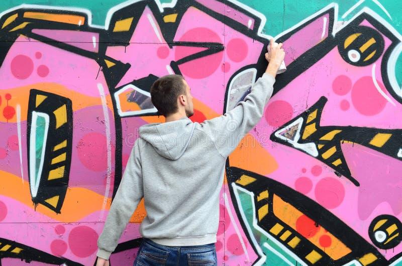 Młody facet w szarym hoodie maluje graffiti w menchiach c i zieleni zdjęcie royalty free