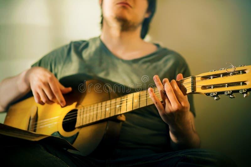 Młody facet z dupkiem na twarzy gra starą melodię na gitarze akustycznej zdjęcie royalty free