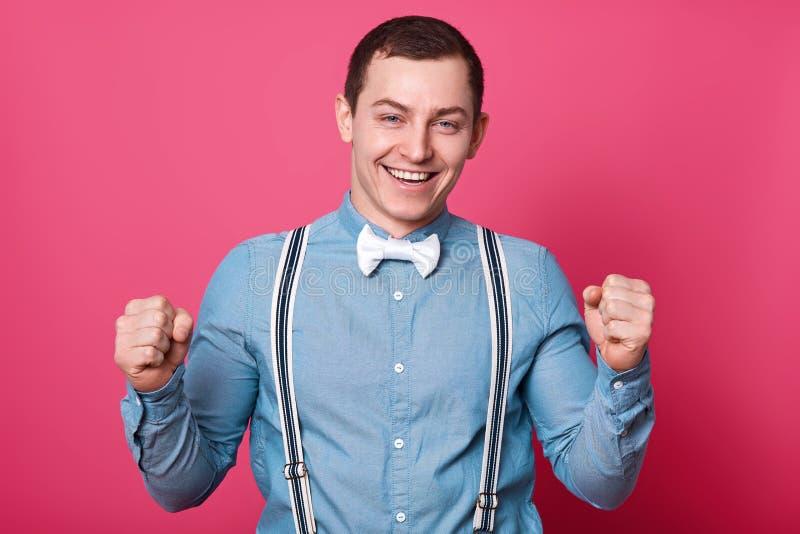 Młody facet z koszula, suspenders i łęku krawatem błękitnymi, świętuje coś z jego pięściami w górę, odizolowywający na różowym tl fotografia royalty free