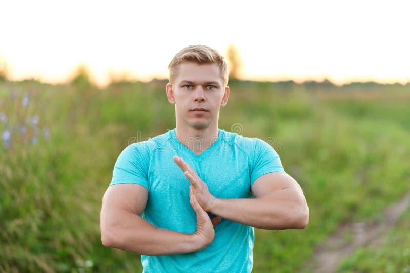 Młody faceta biegacz wcześnie w ranku robi rozgrzewce ręki Lato styl życia pomysł rozgrzewkowy up _ zdjęcie royalty free