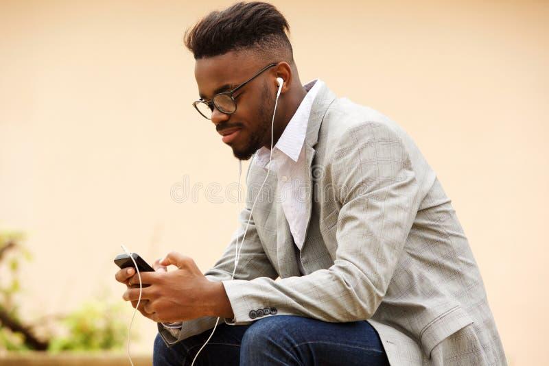 Młody faceta obsiadanie na zewnątrz słuchania muzyka z telefonem komórkowym obraz stock