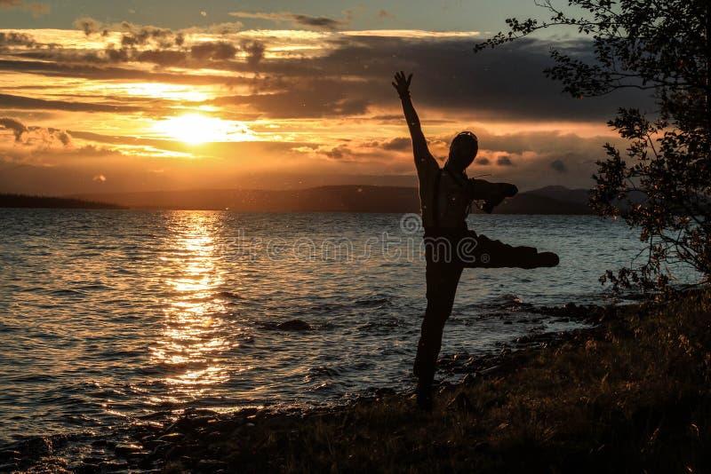 Młody faceta turysta skacze pięknego zmierzch nad jeziorem i cieszy się Muszki latają wokoło on który jarzy się w promieniach, obraz royalty free
