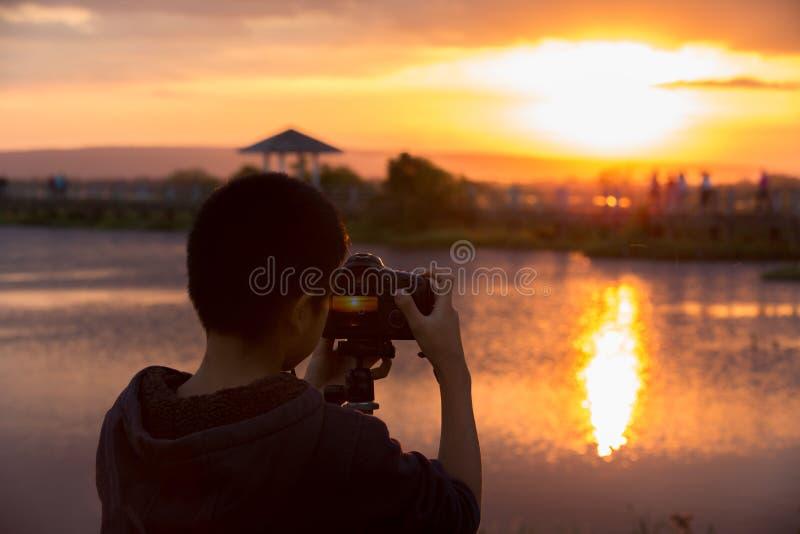 Młody fotograf i Refleksowa kamera na tripod blisko laguny obrazy royalty free
