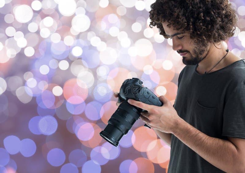 młody fotograf patrzeje fotografie na kamerze Błękita, purpur i bielu bokeh tło, zdjęcie stock