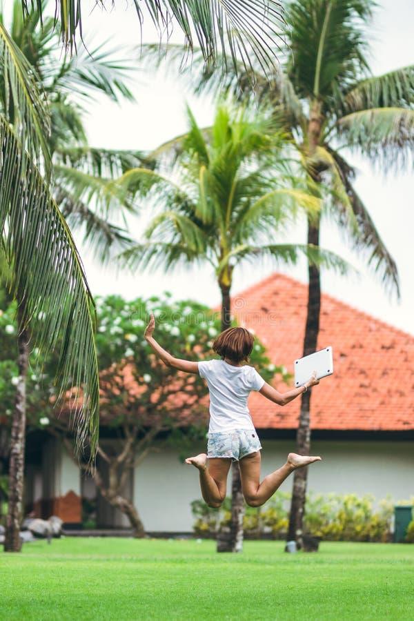 Młody freelancer kobiety doskakiwanie z laptopem w pięknym tropikalnym zieleń parku Bali wyspa zdjęcia royalty free