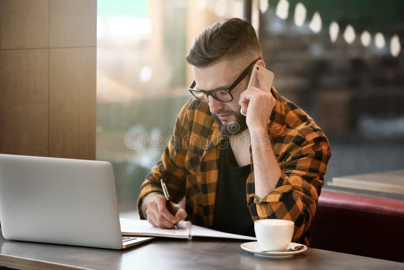 Młody freelancer z telefonem komórkowym i laptopem pracuje w kawiarni zdjęcie royalty free