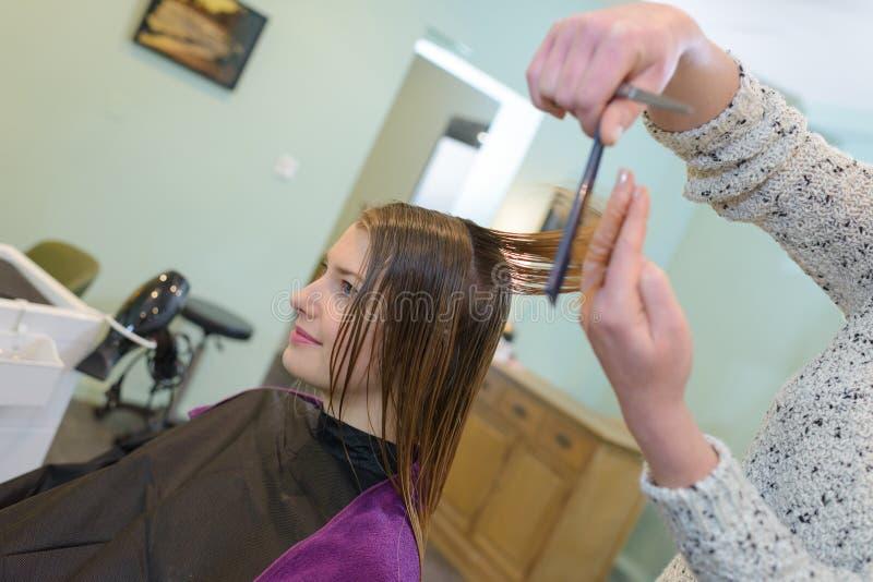 Młody fryzjer daje nowemu ostrzyżeniu żeński klient obraz royalty free