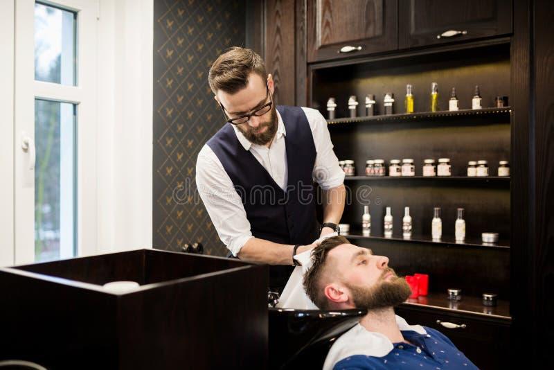 Młody fryzjera męskiego obcierania klienta włosy z ręcznikiem obrazy royalty free