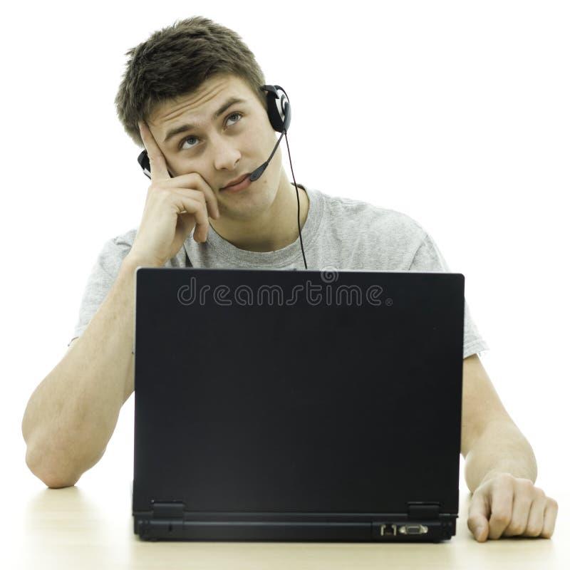 Młody główkowania mężczyzna obsiadanie obok laptopu fotografia stock