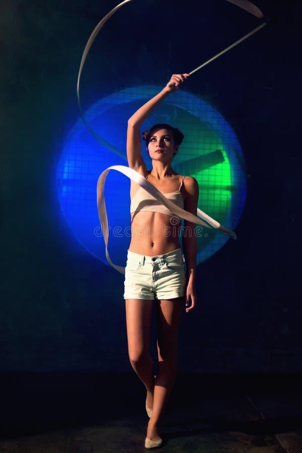Młody gimnastyczki kobiety szkolenie z gimnastyki taśmą na ciemnym tle zdjęcie royalty free