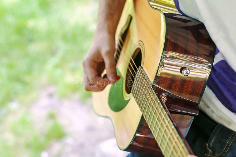 Młody gitara gracz bawić się pieśniowy plenerowego w parku obraz stock