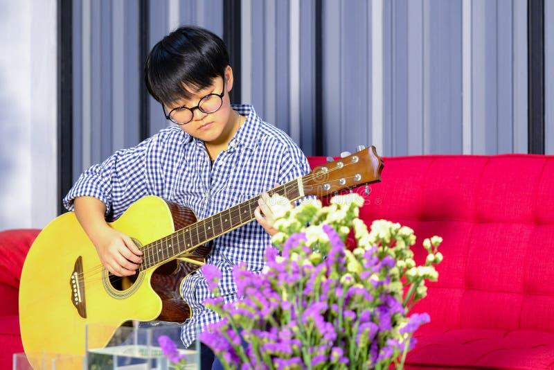 Młody gitarzysty modniś z gitarą na czerwonej kanapie w domu zdjęcie royalty free