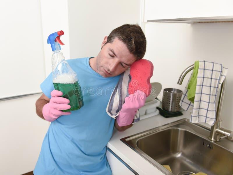 Młody gnuśny domowy cleaner mężczyzna domycie i cleaning kuchni wi fotografia stock