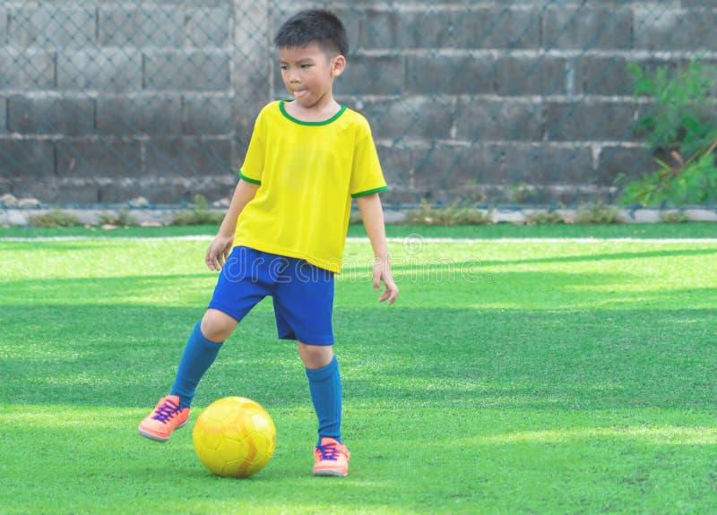 Młody gracz piłki nożnej z żółtą piłką na stażowym polu fotografia stock