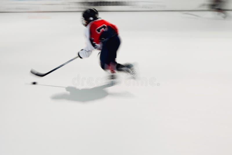 Młody gracz w hokeja w czerwieni sukni z krążkiem hokojowym w ruchu zdjęcia royalty free