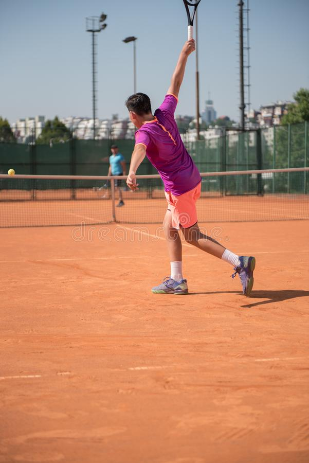 Młody gracz w tenisa bawić się backhand z wysokim wpływem zdjęcia stock