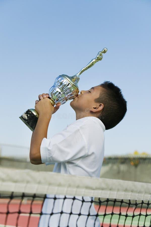 Młody gracz w tenisa siecią na dworskiego całowania trofeum bocznym widoku zdjęcia royalty free